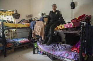 Sgt Conchita Lopez sits on top of a bunk bed