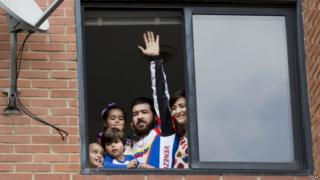 Daniel Ceballos in his Caracas flat with wife and three children