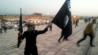 A fighter of the so-called Islamic State group holds an IS flag and a weapon on a street in the city of Mosul, 23 June 2014
