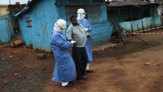Health workers escort an Ebola survivor in Monrovia, Liberia. Photo: October 2014
