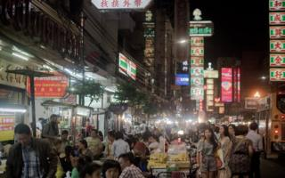 File photo showing people walking past restaurants and street vendors in a Chinatown street in Bankok.
