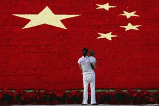 A woman holds her son as she looks at the national flag made up of 100,000 carnations at Wuling Square 25 September 2007 in Hangzhou, China.