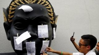 """An opposition student attaches a mock ballot with the option """"No"""" to a statue during a protest against the military-backed draft constitution in Bangkok"""