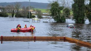 Firemen in waterproof clothing and helmets walk through the waist-high water with an inflatable dinghy. A car is to the right of the picture with water nearly up to the windows. In the background are signs, a lampost and hills and houses.