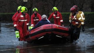 The back of a woman sitting in an inflatable dinghy. She is being pulled by six firemen in rescue outfits and helmets.