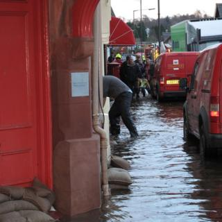 People wading in water up to the middle of their shins, are placing down sand bags outside shop fronts. Royal mail vans driving through the water.
