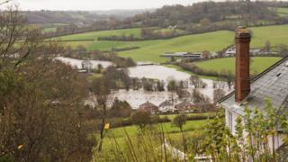 A top shot of a small country village. The river has burst its banks and the fields are flooded.