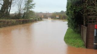A road is flooded with brown water. Either side are hedgerows. A car with lights on is driving through the water.