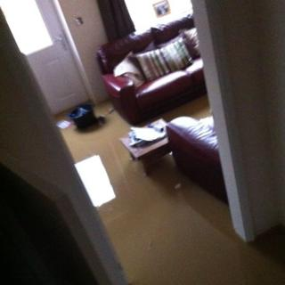 A living room with sofas and a table is flooded.