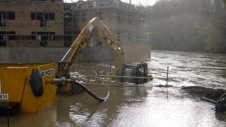 A huge digger is half submerged in brown flood water. Behind is a construction site with scaffolding.