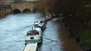 A river with barges on, is overflowing on to the side. Bends, bicycles and lamposts are all in water.