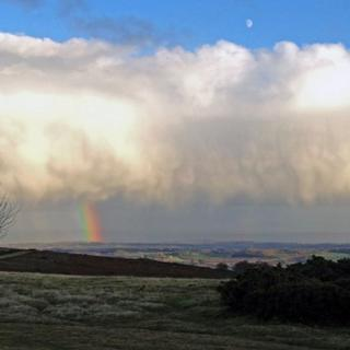 A large wide cloud fills up most of the sky. Below it is a rain-shower and a rainbow; above is clear blue sky and the moon.