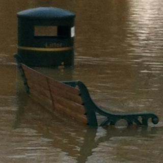 Brown flood water is up to the seating area of a bench and covers over half of a litter bin.