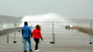 A huge sea spray has come up over a sea wall. The top of a mast can be seen poking through it. A man and a woman look at the scene holding hands behind a barrier; the woman's hair is being blown.