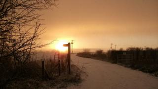 The sun is setting, creating a golden glow over the snow covered fields and pathway.
