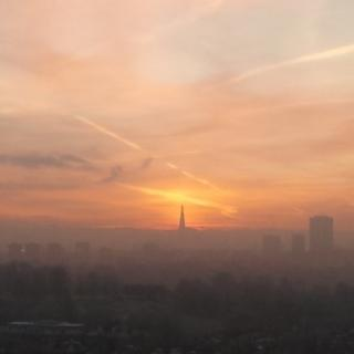 A view of the London skyline in hazy fog. The scene is pink and apricot in colour from the sunrise.