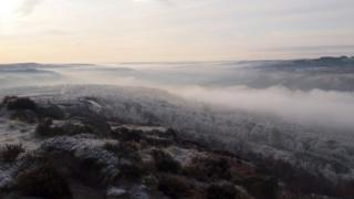 A view from a hill of mist and frosted trees below.