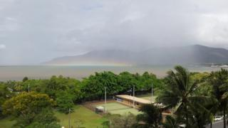 A horizontal rainbow sits on the sea. Above is a rain shower and grey clouds. Tennis courts and palm trees in the foreground.