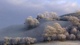 Hills and trees are white in frost.