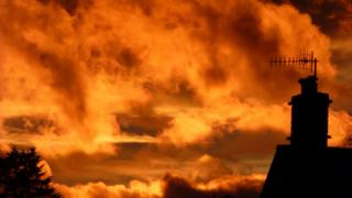 The clouds are orange and yellow in the sky - almost is if they are on fire. Below a chimney and tree are silhouetted.