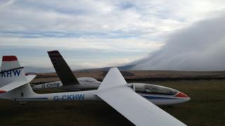 Two small planes in a field. Behind a thick fog cloud is coming in over the land from the right.