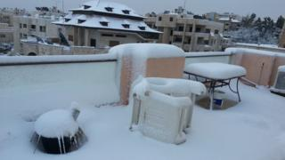 A balcony with tables and furniture on is covered in snow.