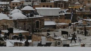 Men on rooftops throwing snowballs at each other. Rooftops and domes have snow on them.