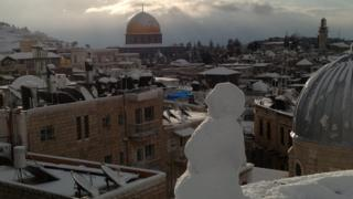 A little snowman looks out from a balcony. His view is the rooftops of the Old City in Jerusalem and the golden Dome of the Rock.