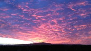 A blanket of cloud on a front, is pink and purple over dark land.