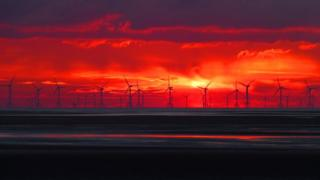 A band of bright red cloud as the sun sets overlooks a windfarm out at sea.