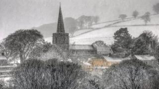 A village scene, with a church, trees, fields and houses is white in the snow. Snow is falling in this shot, making it look slightly blurry.