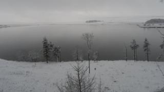 A black and white photo of a large lake. The surrounding land and trees are white with snow.