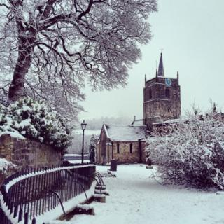 A pretty scene of a church and the surrounding trees covered in snow. There are railings and an old lamp beneath a large tree to the left of the picture.