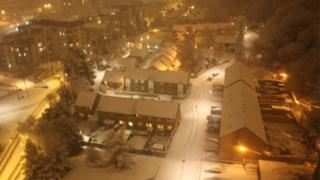 A night time bird's eye view of houses, trees and roads with snow on them. The lights are on and it looks pretty, like everything has been coated in icing sugar.