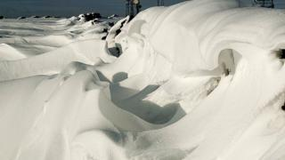 Snow, shaped like waves at sea on top of a hill.