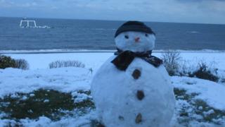 A snowman with hat and scarf in the foreground. Behind is a snowy beach and the sea. In the sea is a white platform with two sculptures - a man and a woman - standing, looking out towards the horizon.
