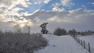 A large telescope in the middle of the picture. Surrounding field and bushes are white in snow. Clouds behind and a bit of blue sky and sun.