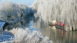 A river with house boats on. Either side the tree branches hang over the river and they are covered in hoar frost.