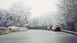 Canal boats on a river. Trees and bushes nearby are covered in snow and frost.