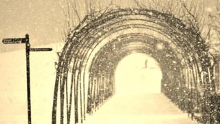 A sepia shot of an arch made out of branches with signposts to the left. All around is snow and it is snowing.