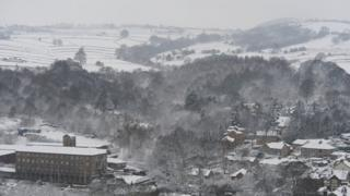 A wide view of a snowy landscape - trees and hills covered in snow. There are houses and buildings in the foreground.