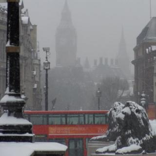 In the foreground are two lion statues, covered in snow and behind is a red London bus. In the background, Big Ben and the Houses of Parliament can just about be seen in the fog.