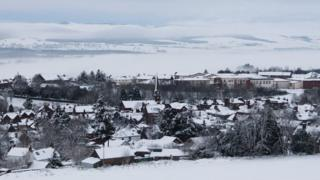 A picturesque scene of a snow covered town and white hills beyond.
