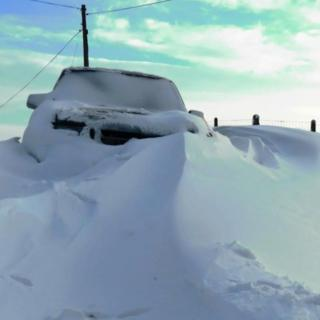 A car caught in a snow drift. Snow piled high up against the front and the windscreen and bonnet are covered in snow.