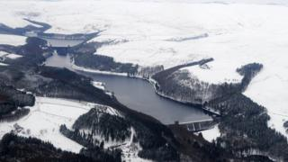 A bird's eye view of a reservoir with snow on the trees, fields and hills around.