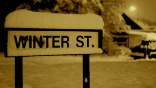 "A street sign saying 'Winter Street"" is covered in snow."