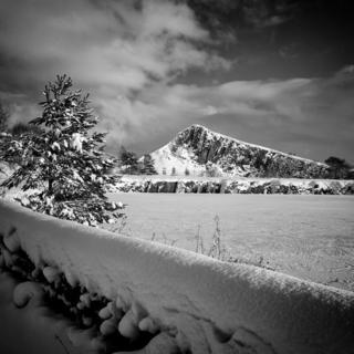 A black and white photo of a lake covered in snow. A fir tree is to the left, also covered in snow and a wall in the foreground frames the picture.