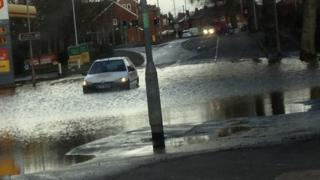 A flooded section of road. A car trying to drive through it.