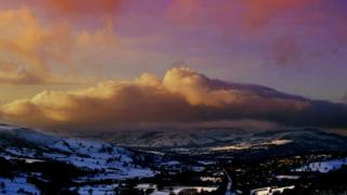 A view of snoy fields and mountains. Over them all is a band of cloud and a purple and yellow sky above.