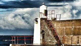 A wall with a lighthouse on it. The sea behind is overseen by large clouds.